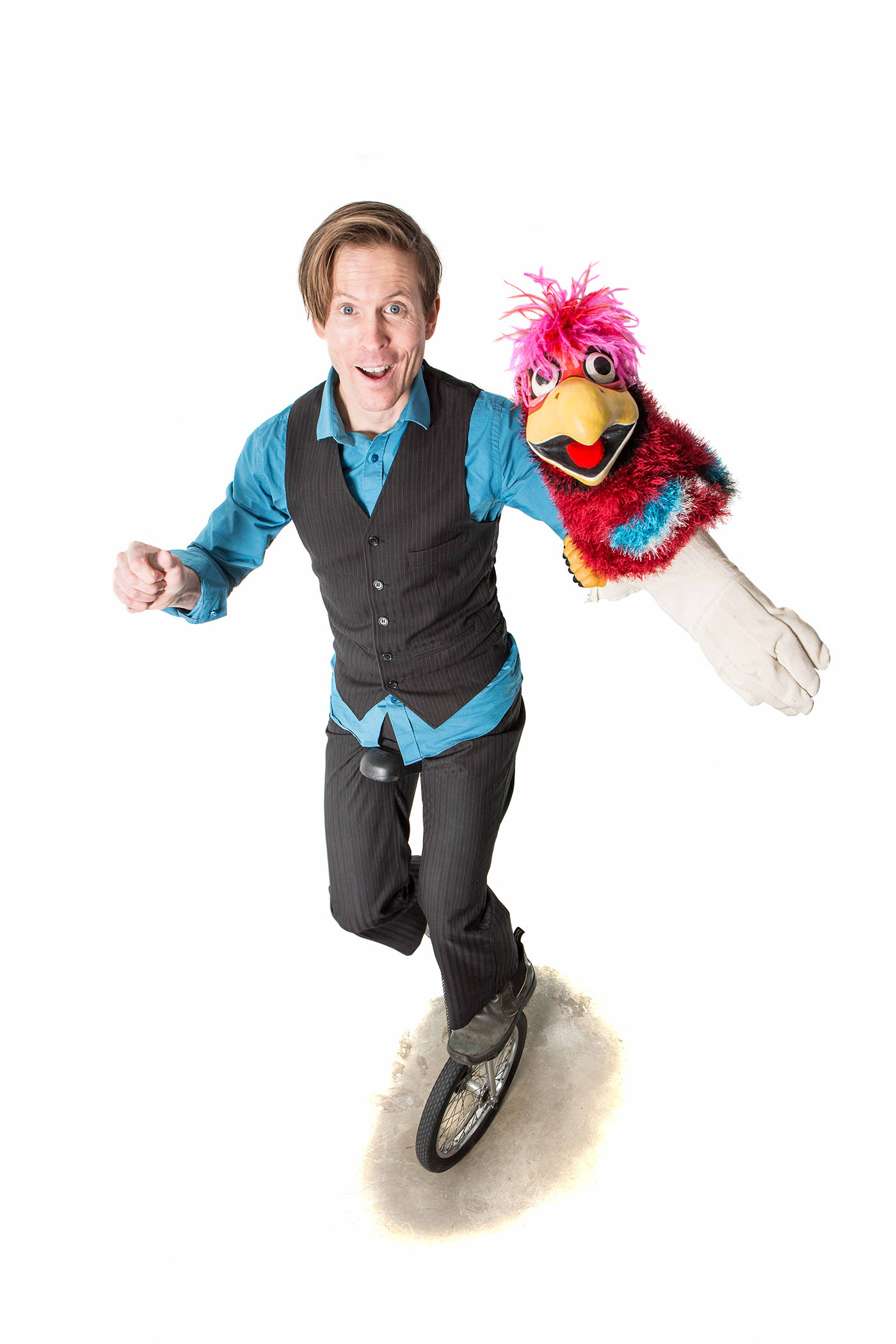 Tim on unicycle with parrot puppet